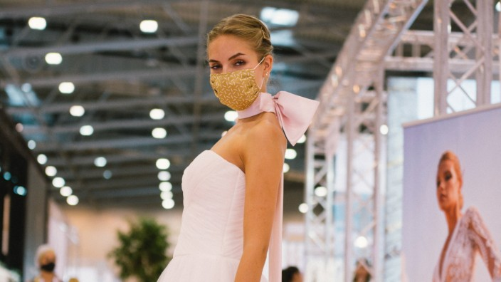 (200705) -- ESSEN (GERMANY), July 5, 2020 -- A model wearing a face mask presents a wedding dress at the European Brida