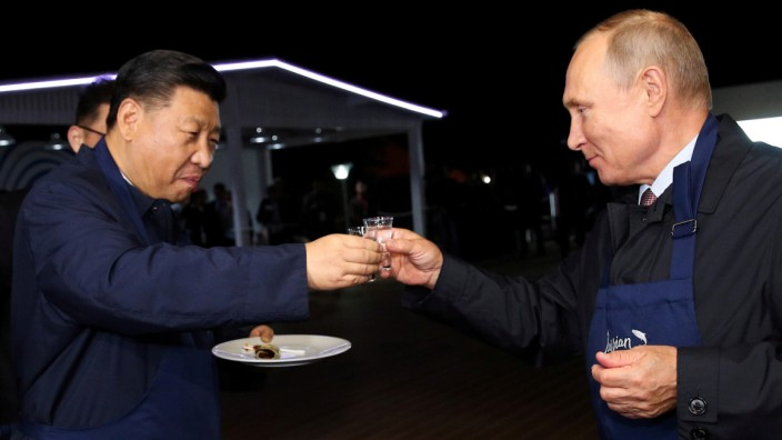 Russian President Vladimir Putin and Chinese President Xi Jinping toast during a visit to the Far East Street exhibition on the sidelines of the Eastern Economic Forum in Vladivostok