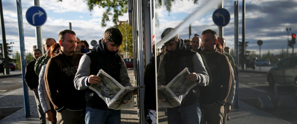 FILE PHOTO -  People wait in line to enter a government-run employment office in Madrid