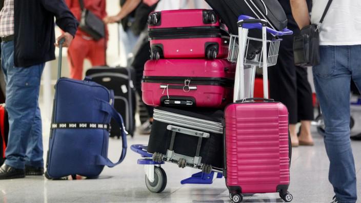 Reisende warten mit Koffern am Flughafen