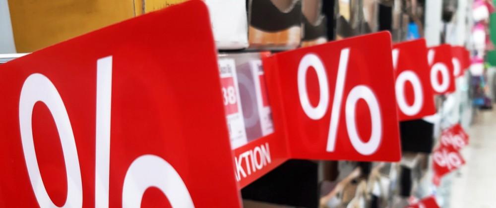 Rote Schilder prangen an Regalen im Supermarkt und kuenden von guenstigeren Preisen fuer den Kunden. Mehrwertsteuersenku