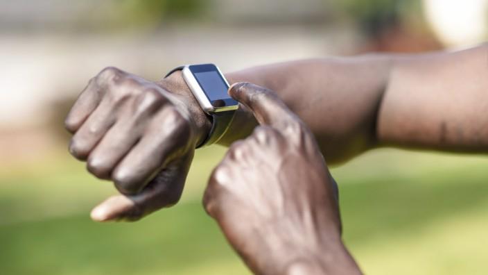 Internationalter Tag der Linkshänder am 13. August Runner checking smart watch fitness tracker, close-up model released