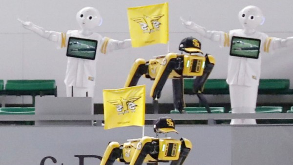 SoftBank Corp's humanoid robots Pepper and Boston Dynamics' robots SPOT in baseball uniforms cheer the team next to empty spectator seats at a baseball game between SoftBank Hawks and Tohoku Rakuten Golden Eagles in Fukuoka, Japan