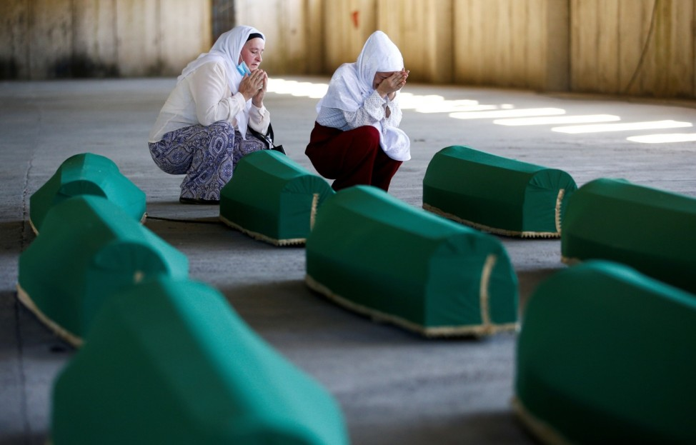 Relatives hold vigil next to coffins with remains of seven newly identified victims at Potocari-Srebrenica Memorial ahead of burial on July 11, in Potocari