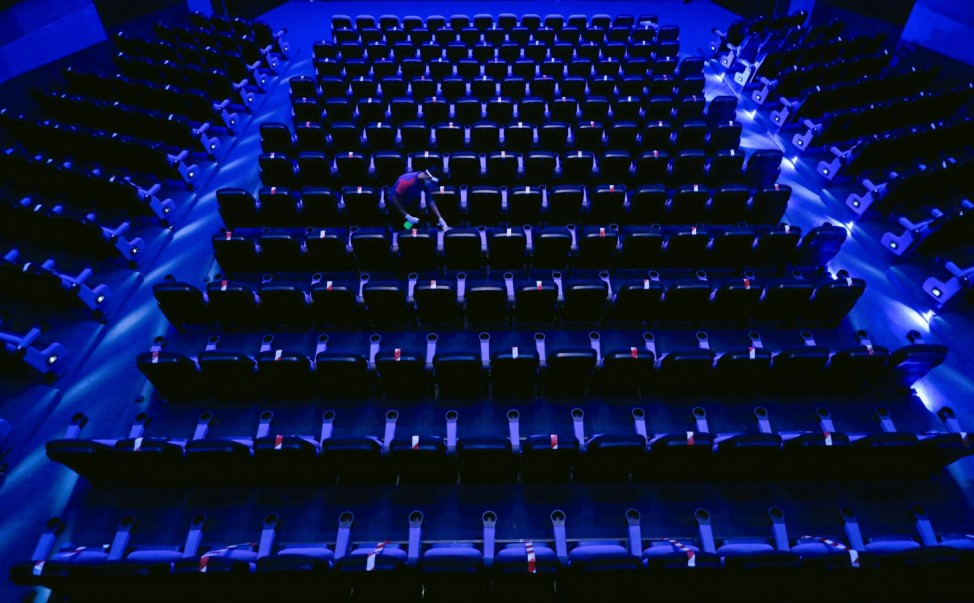 A staff member disinfects the seats after a movie at Savoy cinema, amid concerns about the spread of the coronavirus disease (COVID-19), in Colombo