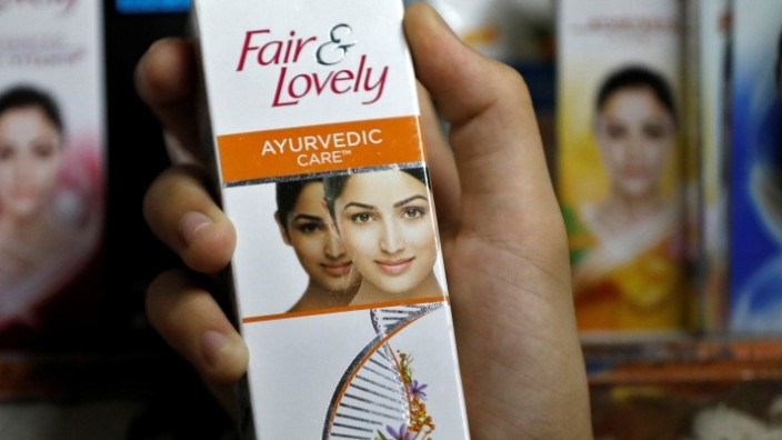 A customer picks up 'Fair & Lovely' brand of skin lightening product from a shelf in a shop in Ahmedabad