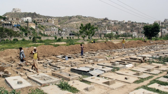 People arrange graves at a cemetery where victims of the coronavirus disease (COVID-19) are buried in Taiz