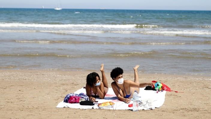 Menschen mit Mund-Nasen-Schutz am Strand