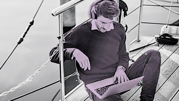 Businessman on a houseboat using laptop wearing headphones model released Symbolfoto property relea