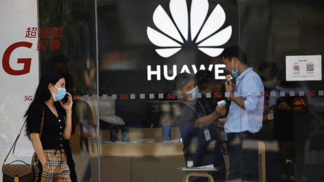 Staff member measures the body temperature of a man inside a Huawei store at a shopping complex in Beijing