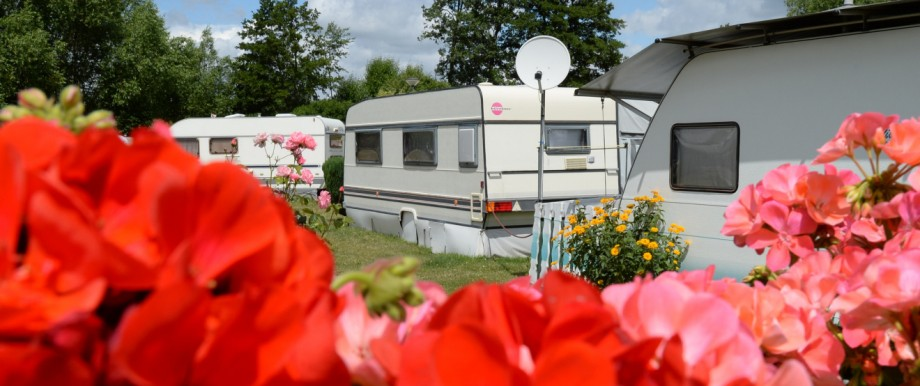 Wohnwagen stehen auf einem Campingplatz.