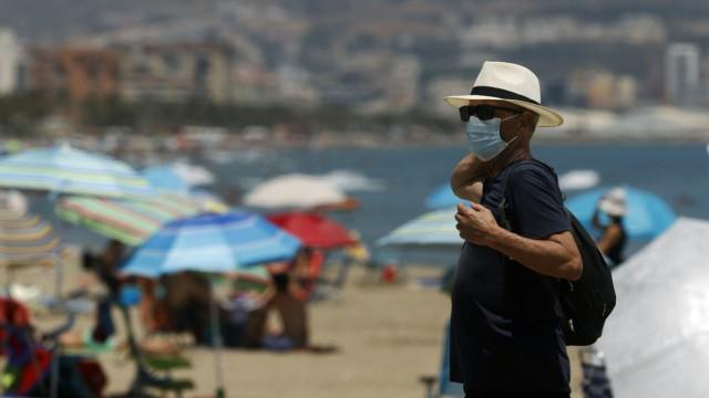 Ein Urlauber mit Mundschutz steht an einem Strand in Malaga in Spanien.