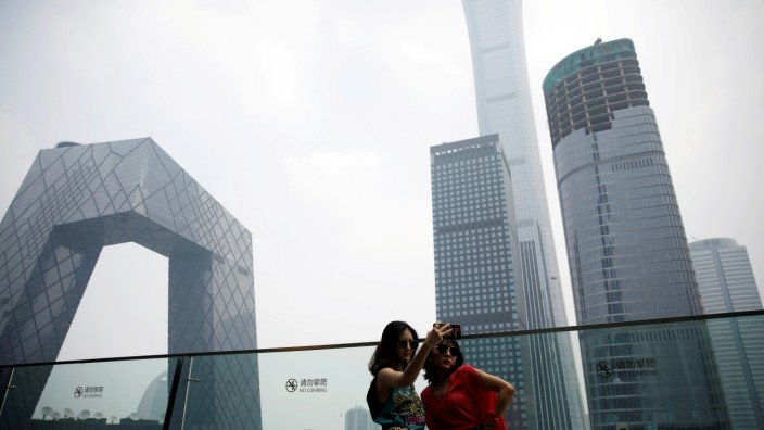 Women pose for pictures at a shopping mall near the CCTV headquarters and China Zun skyscraper in Beijing