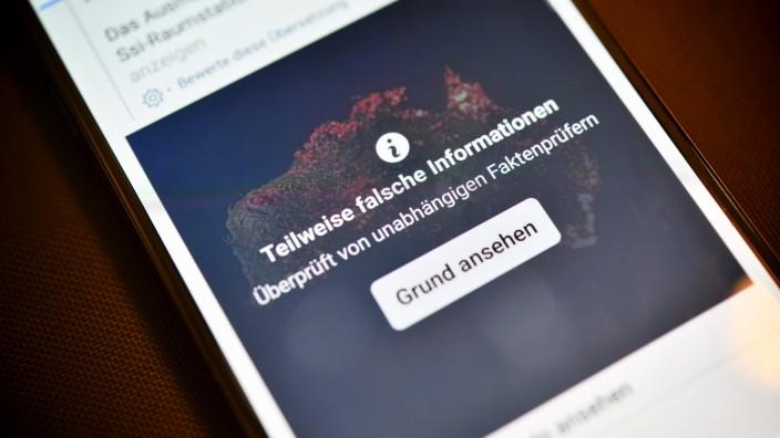 Smartphone mit aufgedeckter Falschinformation in einem sozialen Netzwerk *** Smartphone with revealed false information