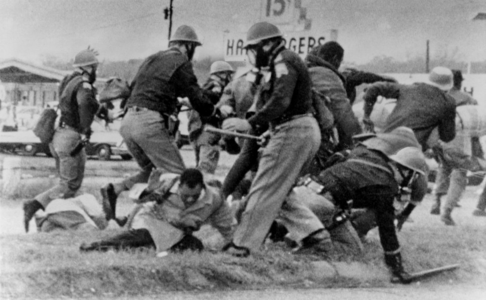 SNCC leader John Lewis (light coat in center) cringes as an Alabama State Trooper swings his club at Lewis head. Lewis w