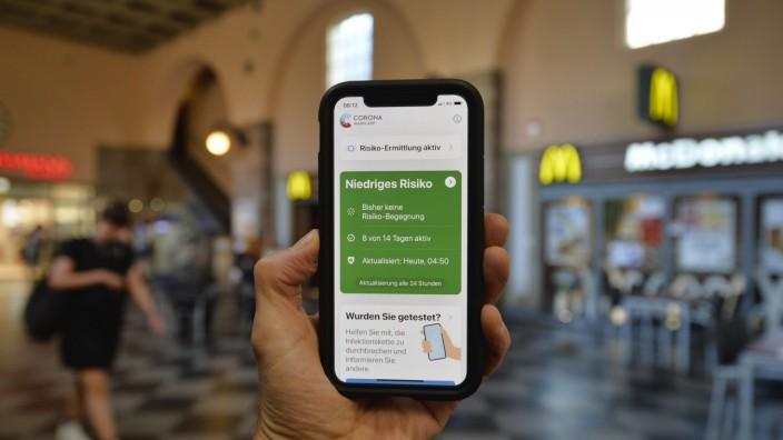 Hand hält Smartphone mit Corona Warn-APP im Bahnhof, Corona-Krise, Stuttgart, Baden-Württemberg, Deutschland Coronaviru