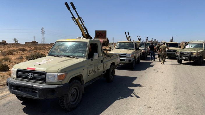Troops loyal to Libya's internationally recognized government are seen in military vehicles as they prepare before heading to Sirte