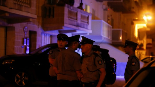 Police officers stand near the home of Melvin Theuma, who had been granted a presidential pardon to testify against the alleged mastermind behind the assassination of anti-corruption journalist Daphne Caruana Galizia, in Swieqi