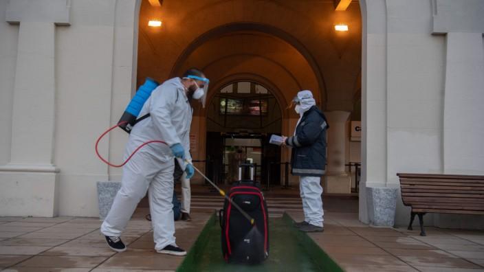 Lateinamerika: Ein Mitarbeiter desinfiziert ein Gepäckstück am Busterminal des Flughafens in Montevideo.