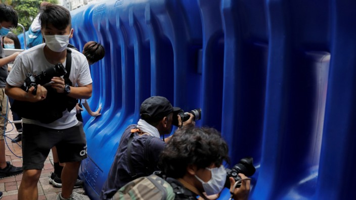 Journalists film behind water filled barriers after the opening ceremony of a temporary national security office, in Hong Kong