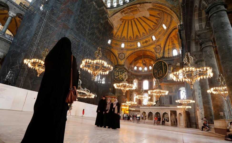 Visitors pose for a picture at Hagia Sophia or Ayasofya, a UNESCO World Heritage Site, in Istanbul