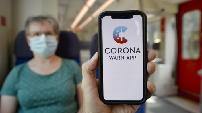 Hand hält Smartphone mit Corona Warn-App vor ältere Frau mit Mundschutzmaske sitzt in S-Bahn, Zug, Corona-Krise, Stuttg