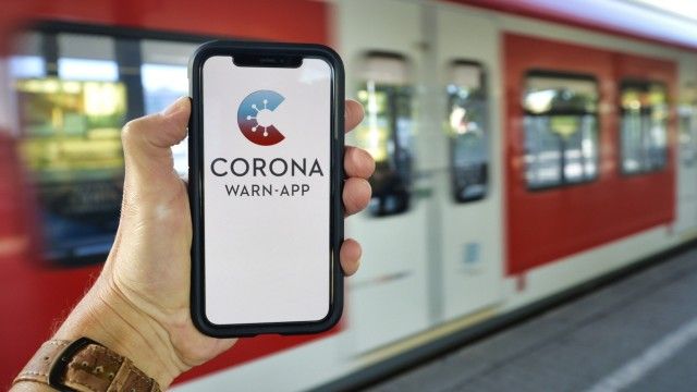 Hand hält Smartphone mit Corona Warn-APP am Bahnsteig, Corona-Krise, Stuttgart, Baden-Württemberg, Deutschland Coronavi
