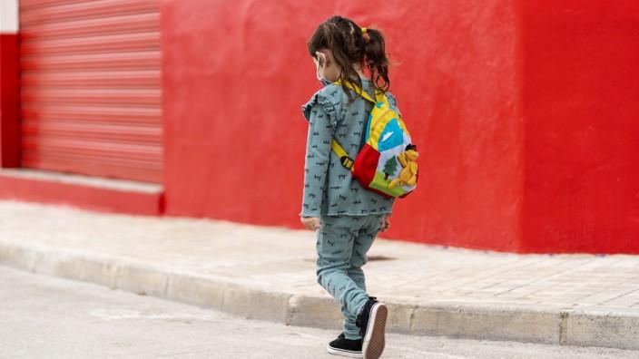Girl walking with backpack and mask on street model released Symbolfoto EGAF00113