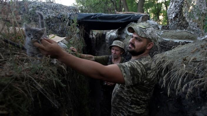 Ukrainian servicemen are seen at a position on the front line near Novotoshkivske
