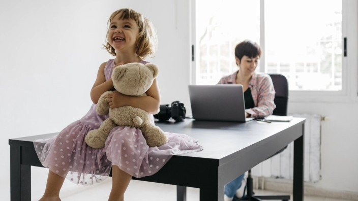 Mother working at home, daughter sitting with teddy bear on table model released Symbolfoto property released JRFF04360