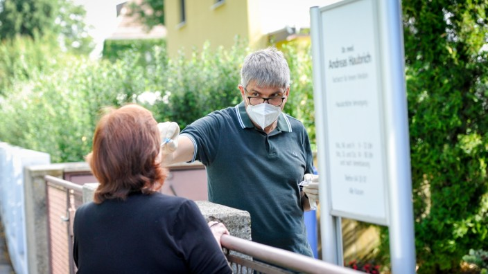 Coronavirus in München: Andreas Haubrich macht den Abstrich bei sich im Garten - hier zwar nur fürs Foto, im Alltag aber auch mit echten Patienten.