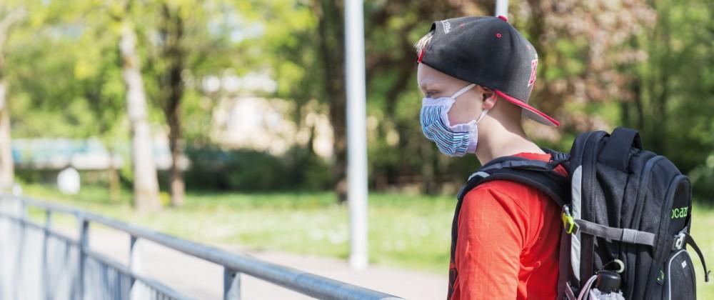 06.05.2020, Corona-Maï¬'nahmen - Maskenpflicht und Schule Ein Junge mit einer Mund-Nasen-Behelfs-Maske und Schulranzen st