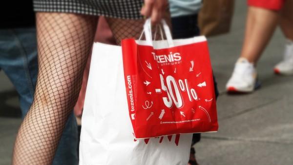 junge Frau im kurzen Rock und Netzstr¸mpfen trâÄ°gt Papiert¸ten von Tezenis und H&M in der Innenstadt von Frankfurt, Hesse