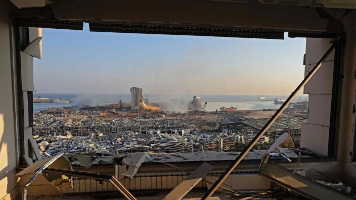 Libanon: Am Morgen nach der Explosion: Blick aus einem von der Druckwelle beschädigten Haus auf den zerstörten Hafen Beiruts, den Ort der Detonation.