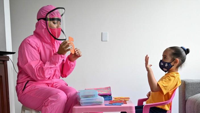 Coronavirus: Um sich gegen eine Ansteckung mit dem Coronavirus zu schützen, unterrichtet eine Lehrerin in der kolumbianischen Stadt Cali ein Mädchen im Schutzanzug. In Kolumbien tauchte die Variante My erstmals auf.