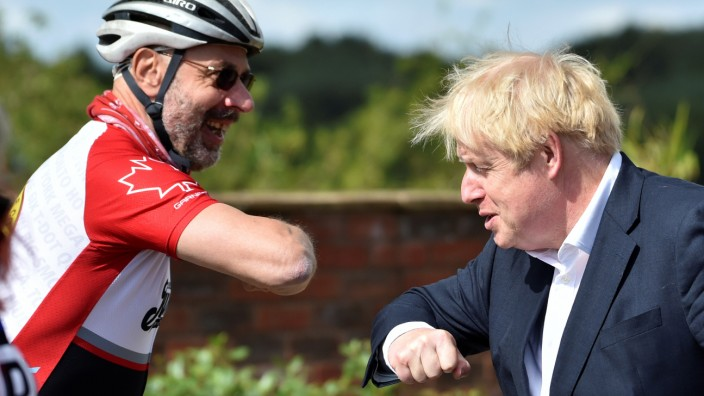 Britain's Prime Minister Boris Johnson bumps elbows with cyclist Robert Cleave the Canal Side Heritage Centre in Beeston