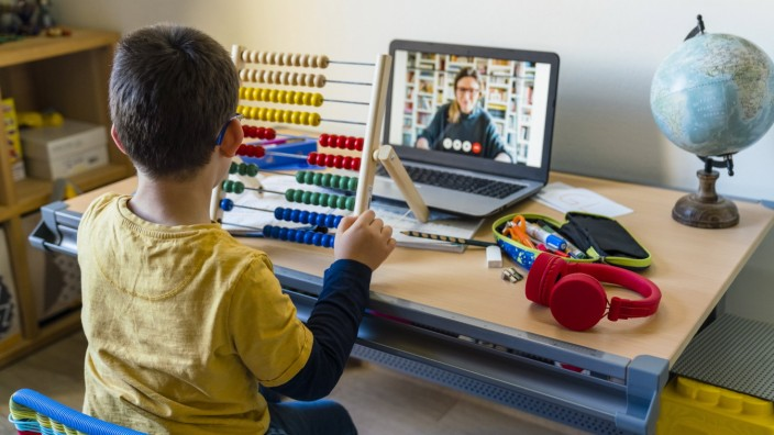 Boy using abacus with teacher on video call during homeschooling model released Symbolfoto property released MGIF00957