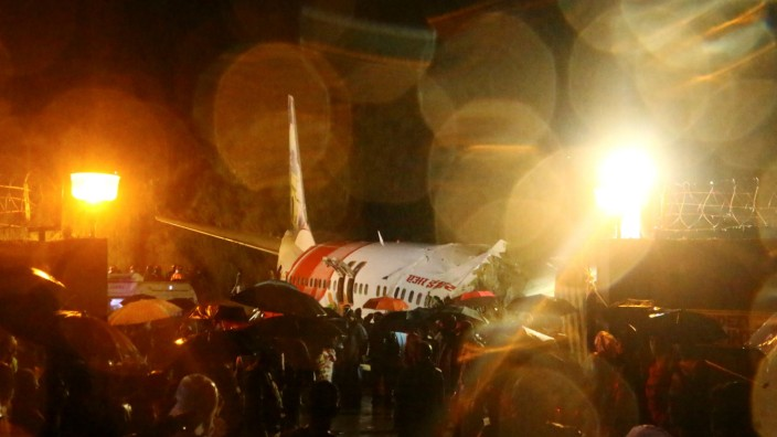 Rescue workers look for survivors after a passenger plane crashed when it overshot the runway at the Calicut International Airport in Karipur