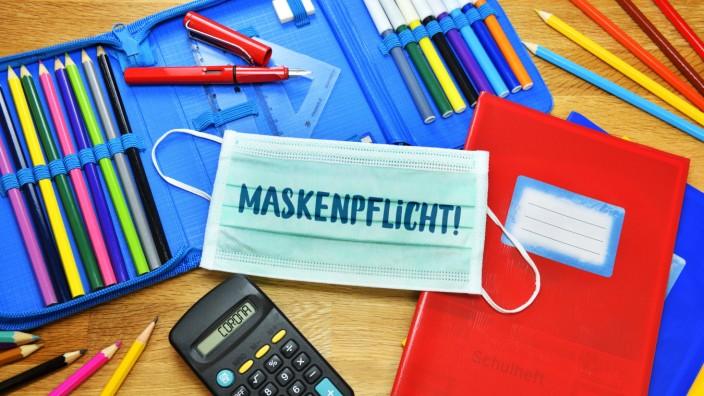 FOTOMONTAGE, Schutzmaske, Federtasche und Stifte, Maskenpflicht an Schulen *** PHOTO MOUNTING, protective mask, pencil
