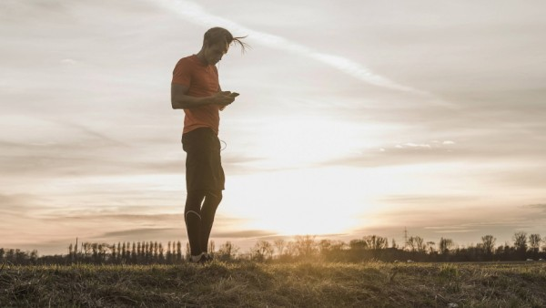 Athlete looking at cell phone in rural landscape at sunset model released Symbolfoto PUBLICATIONxINx