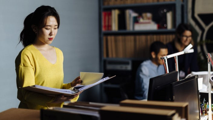 Young woman looking at files in office model released Symbolfoto property released PUBLICATIONxINxGERxSUIxAUTxHUNxONLY S