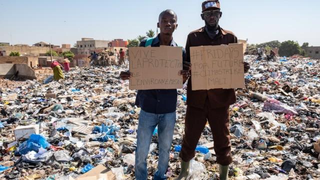 Fousseni Traore et Mohamed, gardien de la GIE qui gère la plateforme  sur laquelle les récupérateurs déposent leurs sacs de matières et d'objets collectés, dépôt 36, commune 4, Bamako, Mali, novembre 2019