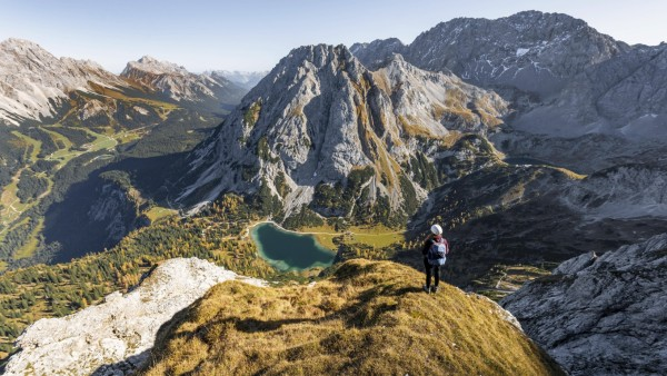 Junge Frau mit Kletterhelm blickt auf Seebensee von der Ehrwalder Sonnenspitze, links Leutaschtal, mitte Vorderer und Hi