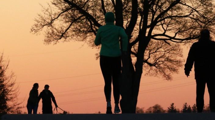 Eine Frau beim Joggen im Freien am Stadtrand von München. Mindestabstand zu den anderen muss eingehalten werden. Wegen d