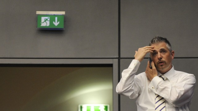 Share trader Dirk Mueller reacts on a phone call as he stands on a gallery above the trading floor of the Frankfurt stock exchange