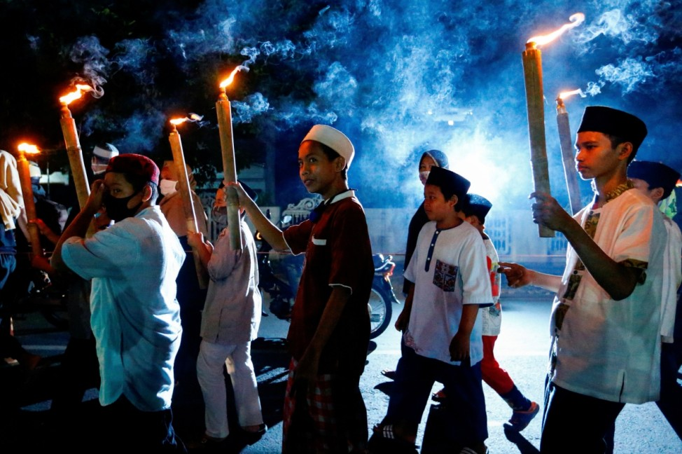 Children carry torches during a parade ahead of the Islamic New Year amid the coronavirus disease (COVID-19) outbreak in Tangerang on the outskirts of Jakarta