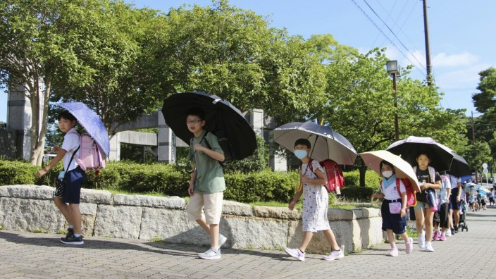 School students with umbrellas in the sun Students head to their elementary school under umbrellas in the sun to maintai