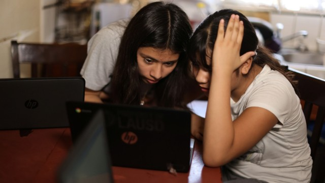 Los Angeles Unified School District (LAUSD) students work on school-issued computers with unreliable internet connectivity, at their home in Los Angeles