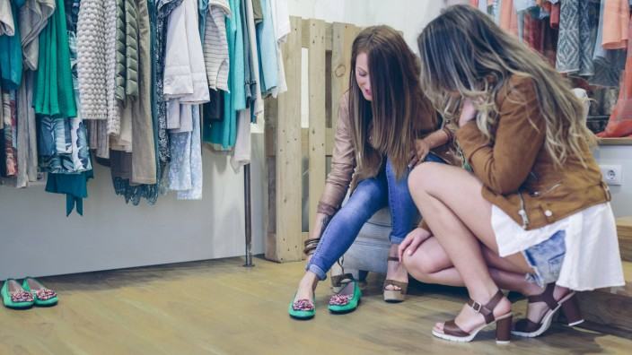 Two women shopping for shoes in a boutique model released Symbolfoto property released PUBLICATIONxI