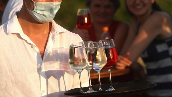 Kellner mit Mund- und Nasenschutzmaske trägt auf der Alte n Brücke in Würzburg ein Tablett mit vollen Weingläsern zu den